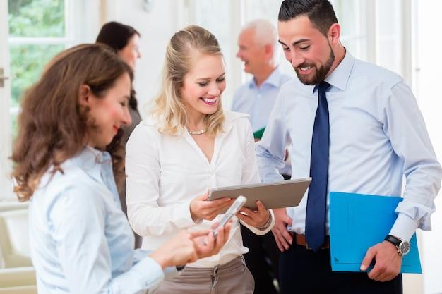 Mensen uit het bedrijfsleven in kantoor met informele bijeenkomst en korte presentatie