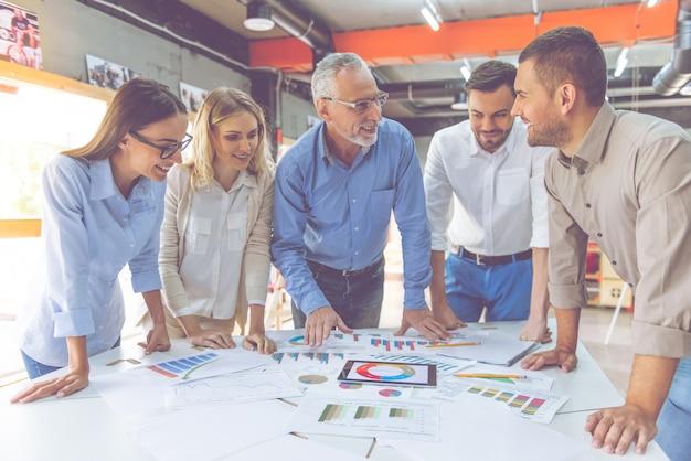 Mensen uit het bedrijfsleven in klassieke shirts bestuderen documenten.