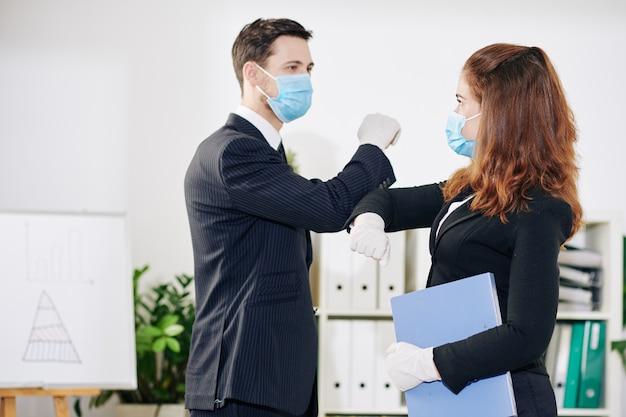 Mensen uit het bedrijfsleven in medische maskers en rubberen handschoenen doen elleboogbult vanwege coronavirus-pandemie wanneer ze elkaar begroeten voordat ze elkaar ontmoeten