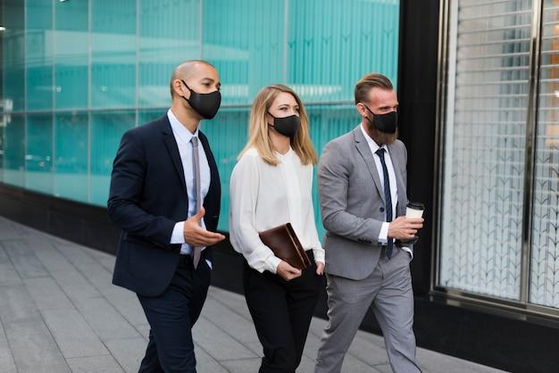 Mensen uit het bedrijfsleven in medische maskers lopen naar het kantoor