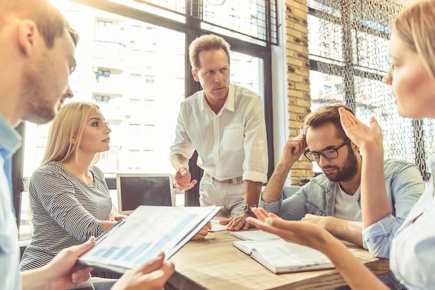 Mensen uit het bedrijfsleven in slimme vrijetijdskleding bespreken.