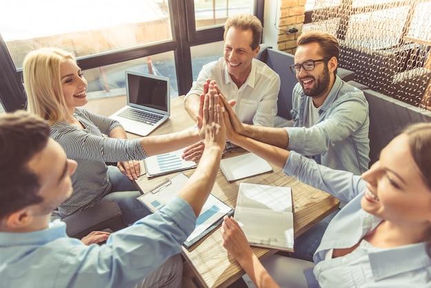 Mensen uit het bedrijfsleven in slimme vrijetijdskleding geven high five