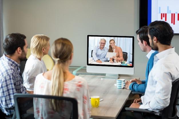 Mensen uit het bedrijfsleven kijken naar een scherm tijdens een videoconferentie