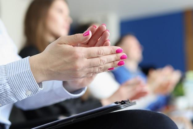 Mensen uit het bedrijfsleven klappen in hun handen en applaudisseren tijdens een vergadering of conferentie
