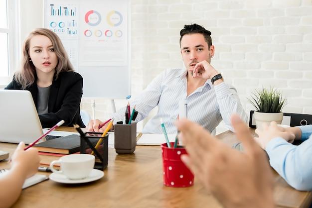 Mensen uit het bedrijfsleven letten op hun collega in vergadering