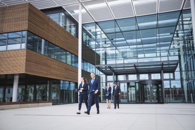 Mensen uit het bedrijfsleven lopen buiten kantoorgebouw