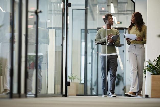 Mensen uit het bedrijfsleven lopen door de kantoorgang en bespreken details van het project waaraan ze werken