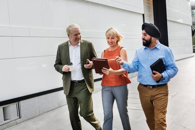 Mensen uit het bedrijfsleven lopen en praten samen in een stad