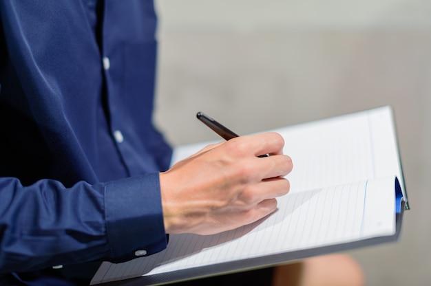 Mensen uit het bedrijfsleven maken aantekeningen in papieren boeken