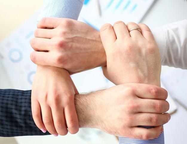 Mensen uit het bedrijfsleven maken routine-teken met handen voor teamspirit boven werktafel