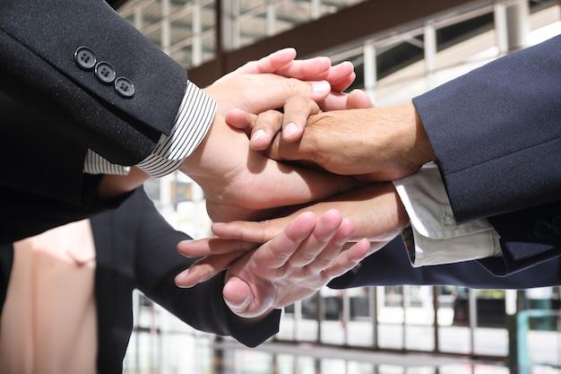 Mensen uit het bedrijfsleven maken stapel handen op kantoor.