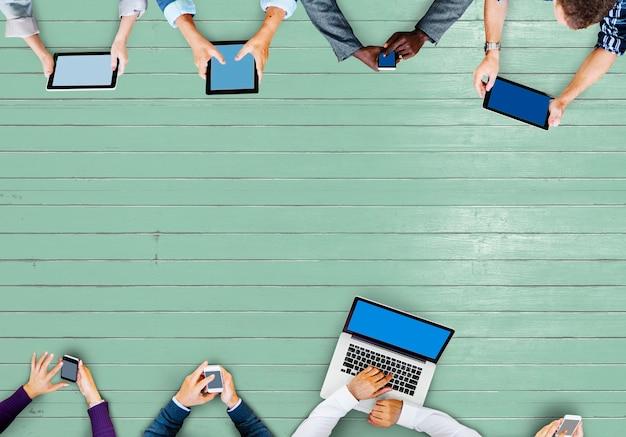 Mensen uit het bedrijfsleven met behulp van digitale apparaten in een vergadering