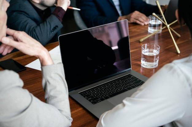 Mensen uit het bedrijfsleven met behulp van een laptop in een vergadering