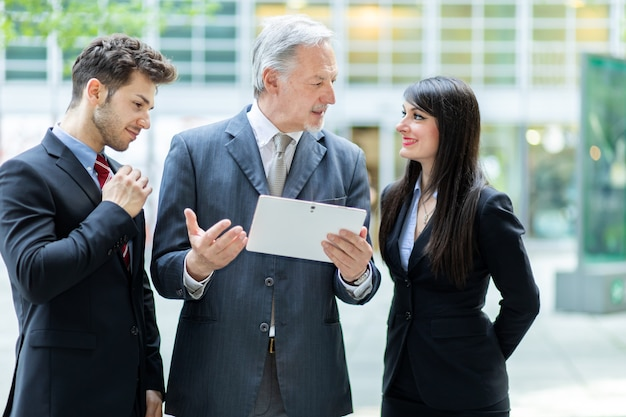 Mensen uit het bedrijfsleven met behulp van een tablet buiten