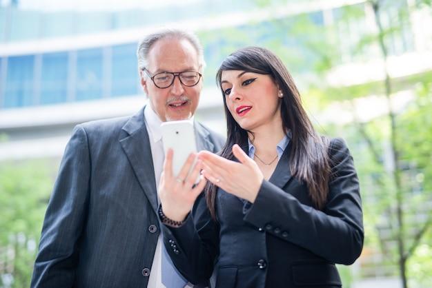 Mensen uit het bedrijfsleven met behulp van een tablet, outdoor kantoorwerkconcept