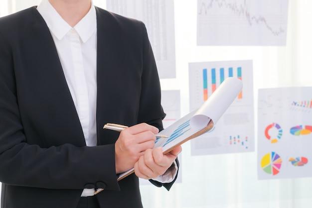 Mensen uit het bedrijfsleven met behulp van en financiële grafieken op de vergadering van het kantoor