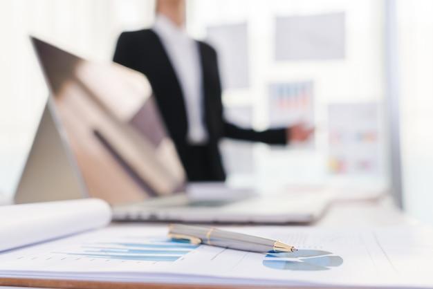 Mensen uit het bedrijfsleven met behulp van laptop en financiële grafieken op de vergadering van o
