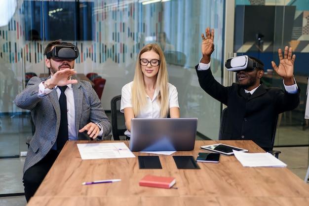 Mensen uit het bedrijfsleven met behulp van virtual reality-bril tijdens vergadering. team van ontwikkelaars die virtual reality-headset testen en nieuwe ideeën bespreken om de visuele ervaring te verbeteren.