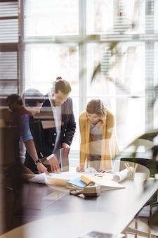 Mensen uit het bedrijfsleven met digitale tablet en blauwdruk