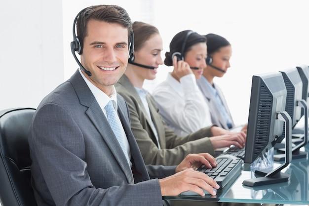 Mensen uit het bedrijfsleven met headsets met behulp van computers op kantoor