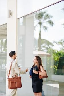 Mensen uit het bedrijfsleven met koffie in de ochtend staan buiten en bespreken details van het werk
