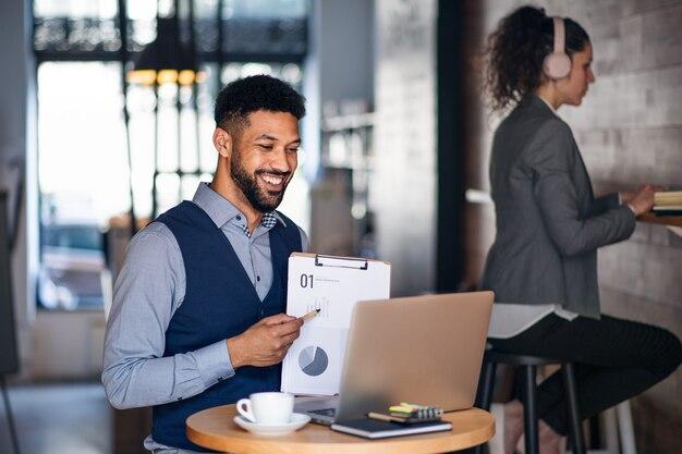 Mensen uit het bedrijfsleven met laptop werken in een café, freelance werk en video-oproep concept.