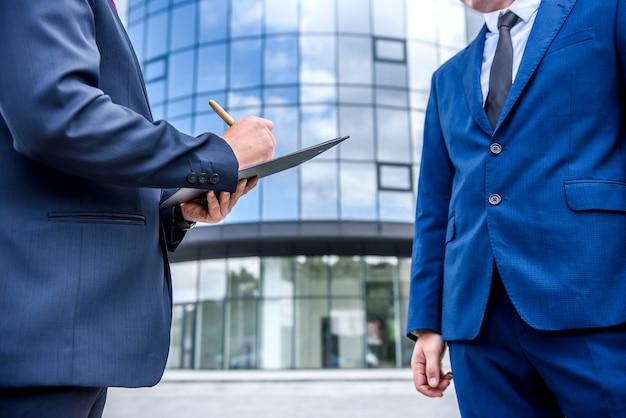 Mensen uit het bedrijfsleven ondertekenen contract in de buurt van wolkenkrabber buitenshuis