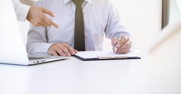 Mensen uit het bedrijfsleven ondertekenen contract maken van een deal met makelaar