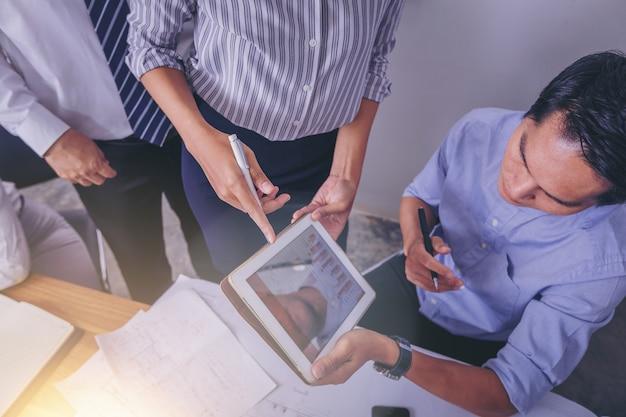 Mensen uit het bedrijfsleven ontmoeten elkaar om de situatie op de markt te bespreken met de touchpad.