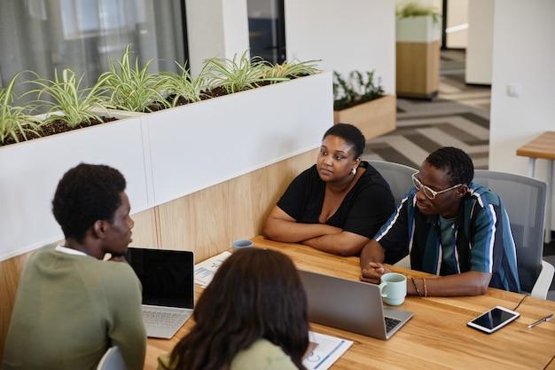 Mensen uit het bedrijfsleven ontmoeten elkaar op kantoor om manieren te bespreken om de economische crisis veroorzaakt door het coronavirus te overwinnen ...