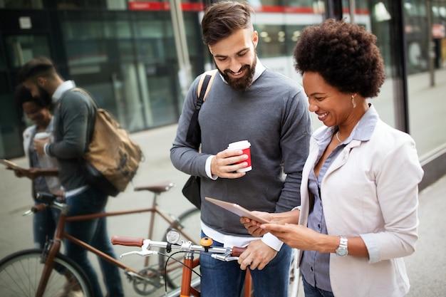 Mensen uit het bedrijfsleven op koffiepauze met behulp van digitale tablet buiten in de stad