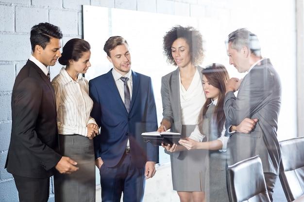 Mensen uit het bedrijfsleven op zoek in dagboek en interactie in vergaderruimte