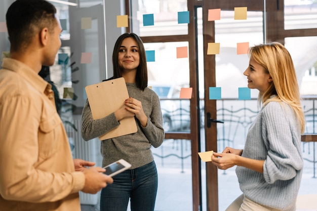 Mensen uit het bedrijfsleven plannen opstarten, werken, met behulp van plaknotities op kantoor