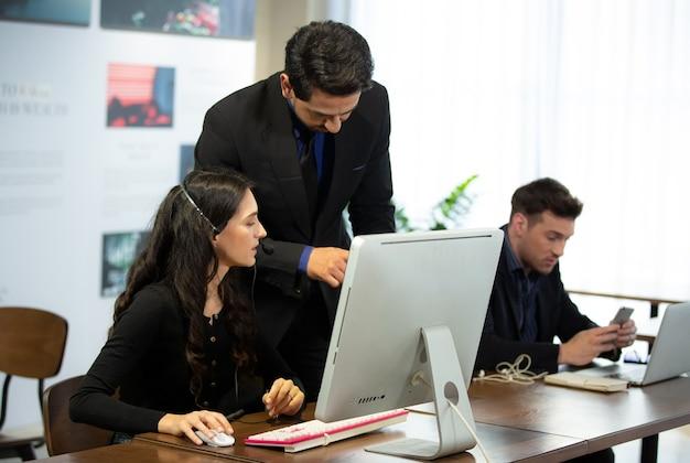 Mensen uit het bedrijfsleven praten in kantoor met behulp van digitale tablet en computer