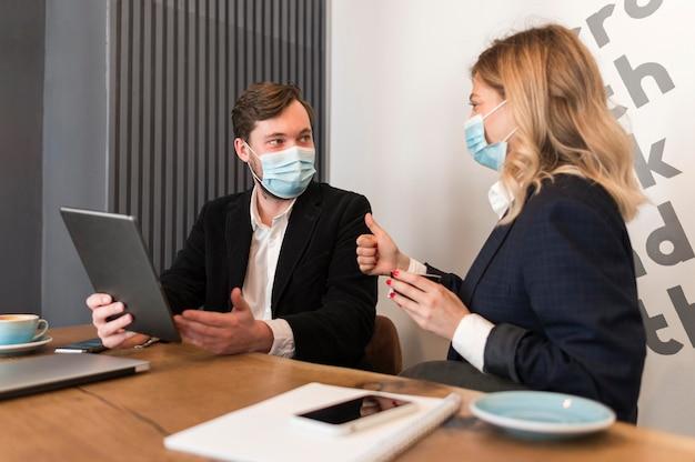 Mensen uit het bedrijfsleven praten over een nieuw project terwijl ze medische maskers dragen