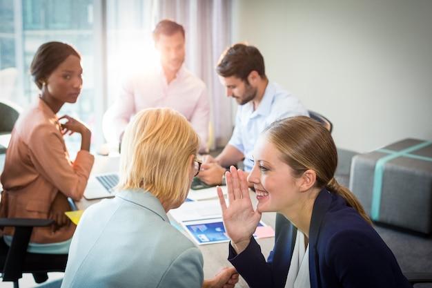 Mensen uit het bedrijfsleven roddelen tijdens vergadering
