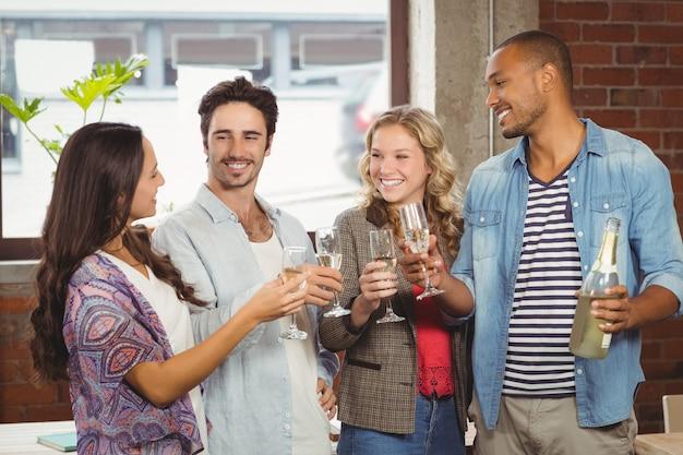 Mensen uit het bedrijfsleven roosteren met champagne op kantoor