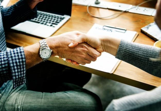 Mensen uit het bedrijfsleven schudden de hand in overleg