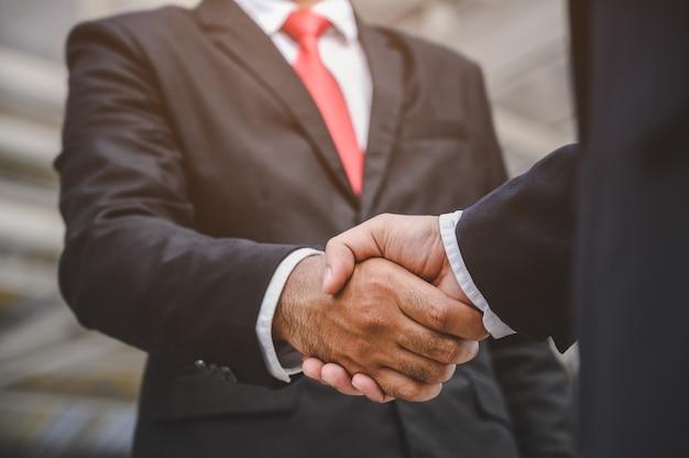 Mensen uit het bedrijfsleven schudden elkaar de hand om een zakelijke voorstelovereenkomst te sluiten ging goed