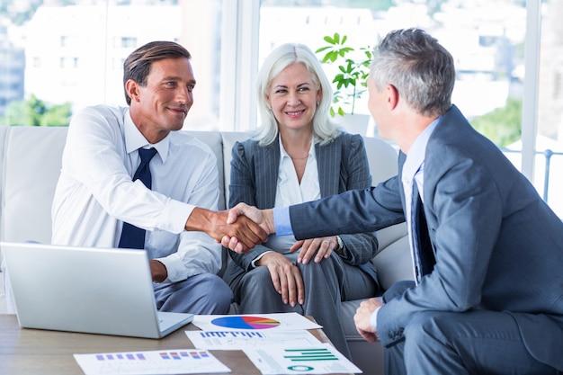 Mensen uit het bedrijfsleven schudden elkaar de hand op de bank