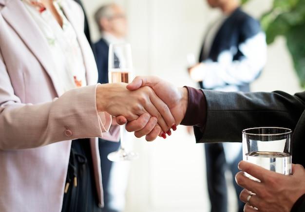 Mensen uit het bedrijfsleven schudden elkaar de hand op een kantoorfeestje