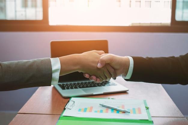 Mensen uit het bedrijfsleven schudden handen om succes in het bedrijfsleven aan te tonen