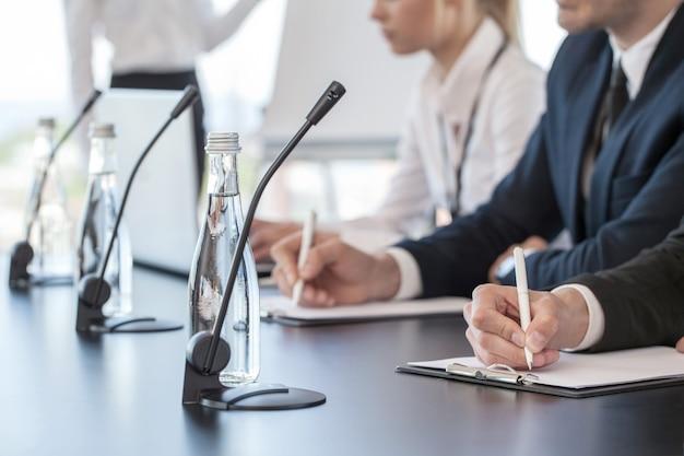 Mensen uit het bedrijfsleven spreken op presentatie in microfoons in kantoor