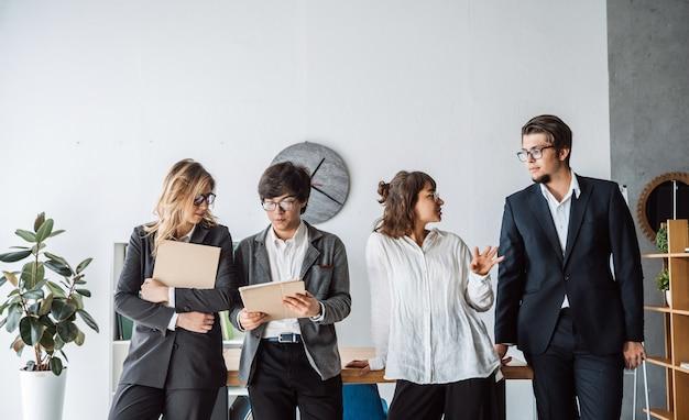 Mensen uit het bedrijfsleven staan in het kantoor bespreken