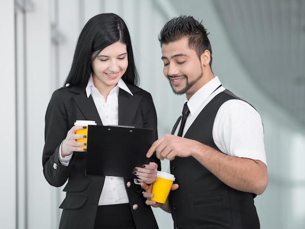 Mensen uit het bedrijfsleven staan in kantoor en drinken koffie.