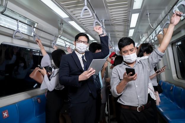 Mensen uit het bedrijfsleven staan in metro massa doorvoer metro. man met behulp van tablet en smartphone. mensen die een gezichtsmasker dragen. coronavirus-griepvirus in openbare reizen.