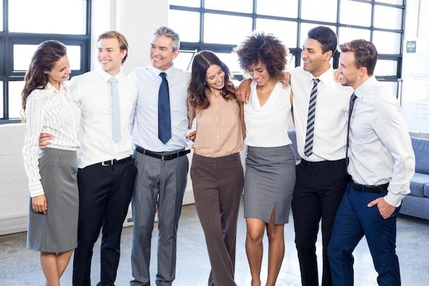 Mensen uit het bedrijfsleven staan samen met armen om elkaar heen in het kantoor