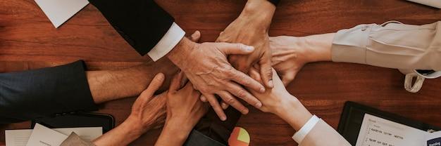 Mensen uit het bedrijfsleven stapelen hun handen op elkaar