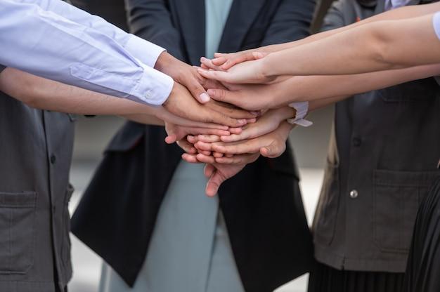 Mensen uit het bedrijfsleven team stapelen handen en teamwork concept.