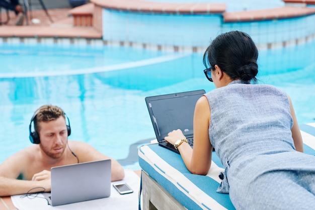 Mensen uit het bedrijfsleven tijd doorbrengen bij het zwembad
